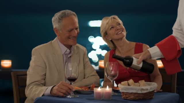 vídeos y material grabado en eventos de stock de senior couple in moonlight having dinner waiter pouring wine - brazo humano