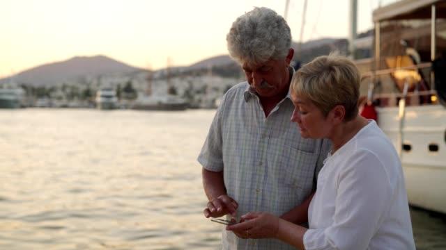 vídeos de stock e filmes b-roll de senior couple is relaxing near the sea - idoso na internet
