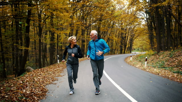 senior couple jogging in a forest. - terza età video stock e b–roll