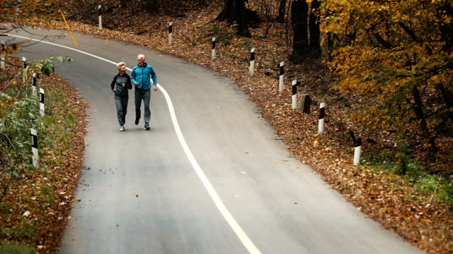 senior couple jogging in a forest. - wide angle stock videos & royalty-free footage