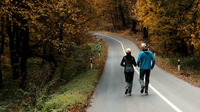 Älteres Paar im Wald joggen.