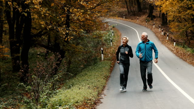 senior couple jogging in a forest. - early morning exercise stock videos & royalty-free footage