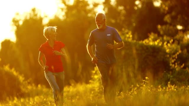 senior couple jogging in a forest. - uomini anziani video stock e b–roll