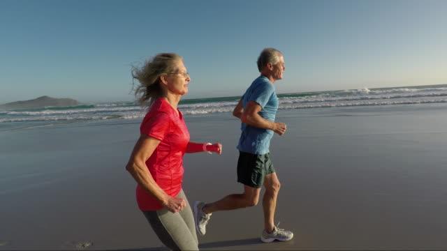 Senior couple jogging on a beautiful beach at sunset
