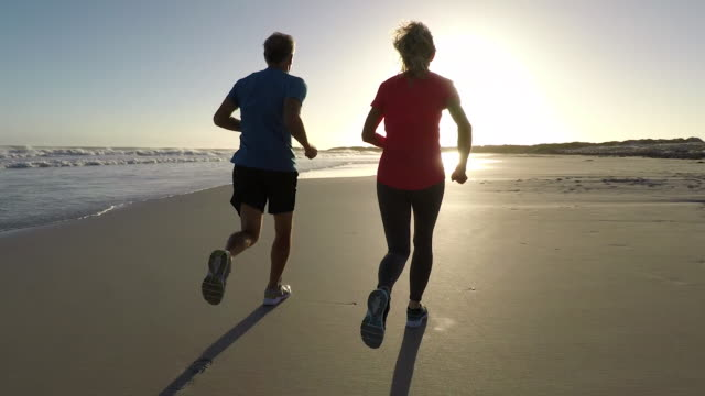 senior couple jogging on a beautiful beach at sunset - sportbegriff stock-videos und b-roll-filmmaterial