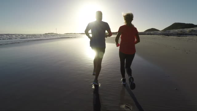 senior couple jogging on a beautiful beach at sunset - 60 64 years stock videos & royalty-free footage
