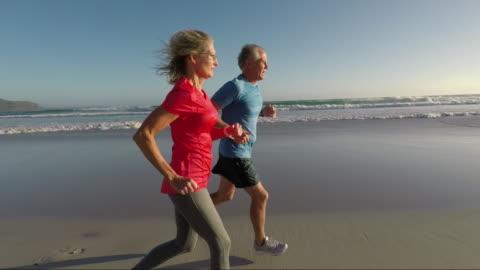 senior couple jogging on a beautiful beach at sunset - aktiva pensionärer bildbanksvideor och videomaterial från bakom kulisserna