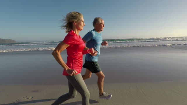 Senior couple jogging on a beautiful beach at sunset