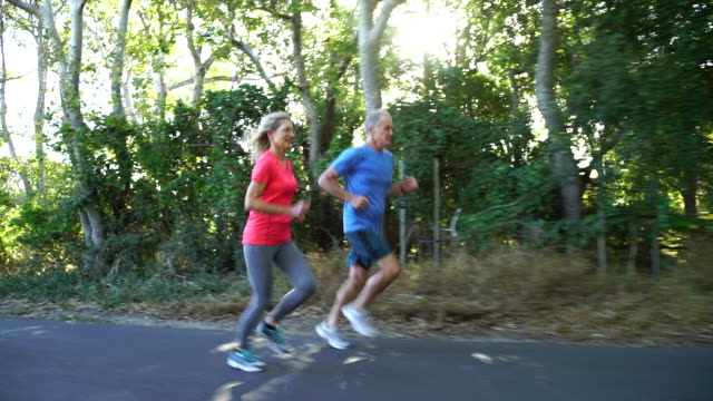 senior couple jogging on a country lane - senior couple stock videos & royalty-free footage