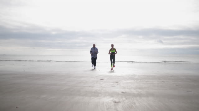 senior couple jogging on beach - kent england stock videos & royalty-free footage
