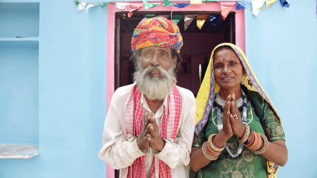 senior couple join hands in namaste greeting with hands joined together to welcome to their house and their hearts - human face video stock e b–roll