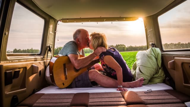 senior couple kissing in a camper van - senior couple stock videos & royalty-free footage