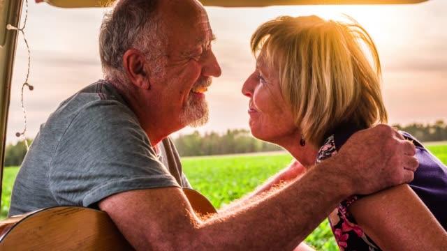 stockvideo's en b-roll-footage met senior paar zoenen in senior paar in open auto kofferbak - romantische activiteit
