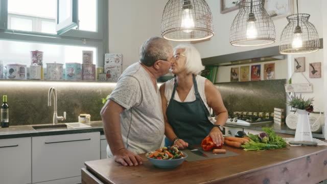 senior couple kissing while preparing salad in family kitchen - flirting stock videos & royalty-free footage
