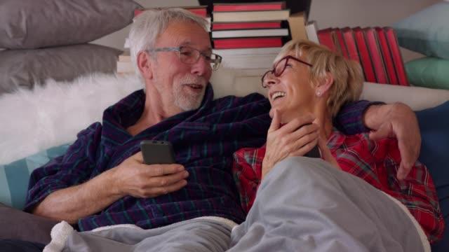 senior-paar lacht und entspannt im bett am morgen - gemütlich stock-videos und b-roll-filmmaterial