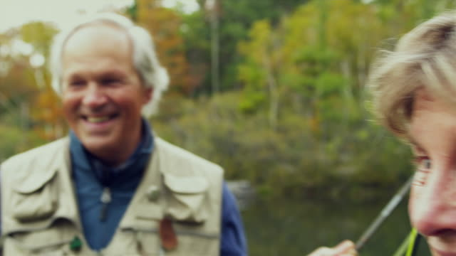 cu r/f senior couple laughing and talking, standing by lake holding fishing rods, manchester, vermont, usa - senior couple stock videos & royalty-free footage
