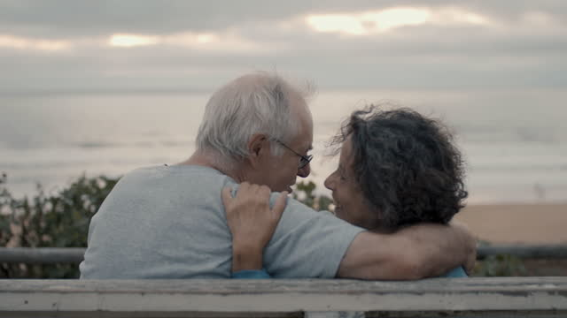 senior couple laughing together at beach - falling in love stock videos & royalty-free footage