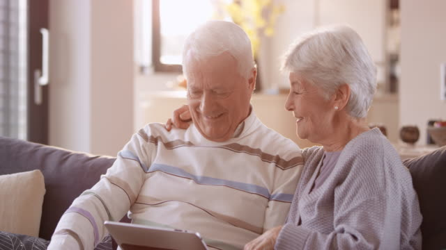 senior couple laughing while watching something on digital tablet - donne anziane video stock e b–roll