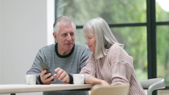senior couple looking at a smartphone together - 70 79 jahre stock-videos und b-roll-filmmaterial