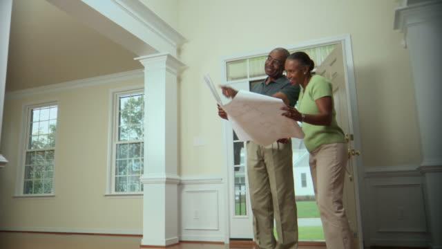 ws, pan, senior couple looking at floor plans in new house, richmond, virginia, usa - grundriss stock-videos und b-roll-filmmaterial