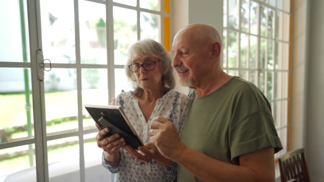 vídeos y material grabado en eventos de stock de pareja de ancianos mirando fotos de sus familias en un asilo de ancianos - marco