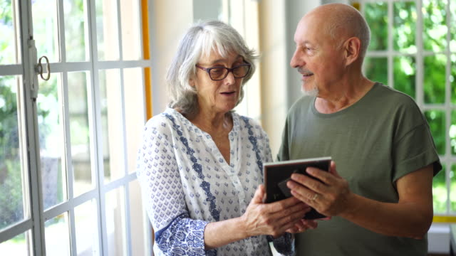 senior couple looking at pictures of their families at nursing home - photograph stock videos & royalty-free footage