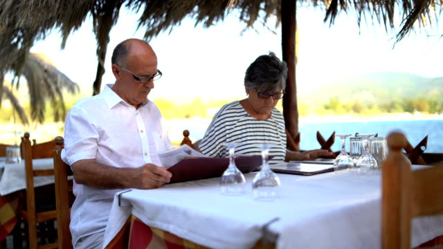 senior couple looking at restaurant menu - order stock videos & royalty-free footage