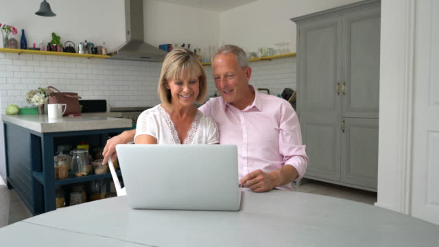 senior couple looking at something on their laptop and talking - husband stock videos & royalty-free footage