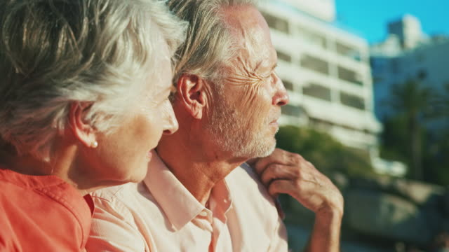 senior couple looking away at beach in summer - stringere tenere video stock e b–roll