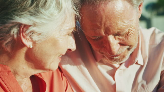 senior couple looking away at beach in summer - senior couple stock videos & royalty-free footage