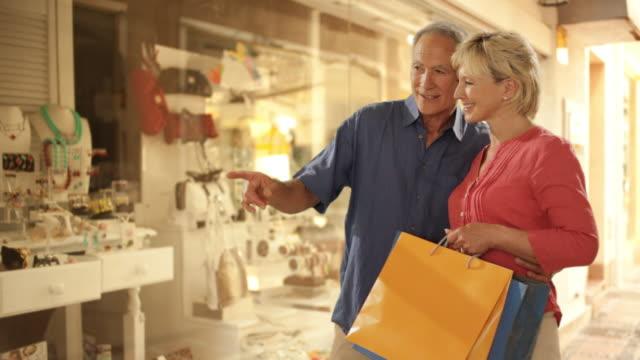 senior couple looking in shop window in town
