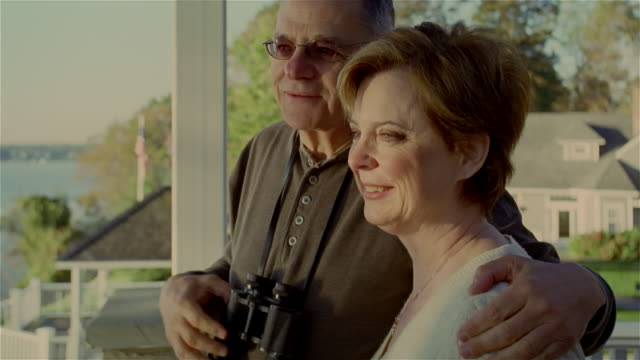 senior couple looking out from deck / hugging - binoculars stock videos & royalty-free footage