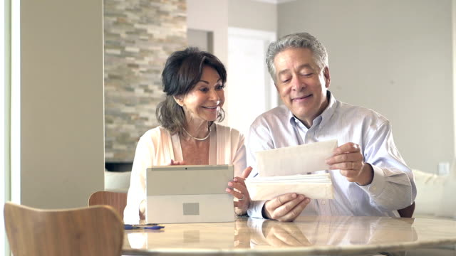 Senior couple looking through mail, paying bills