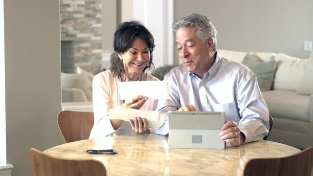 senior couple looking through mail, paying bills - budget stock videos & royalty-free footage