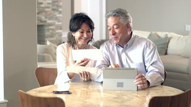 Senior couple looking through mail, paying bills