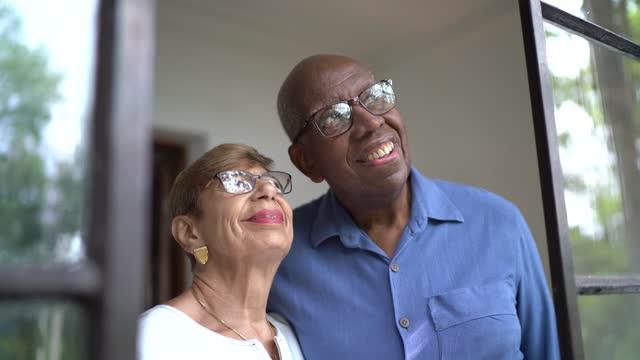 vídeos de stock, filmes e b-roll de casal sênior olhando pela janela em casa - nostalgia