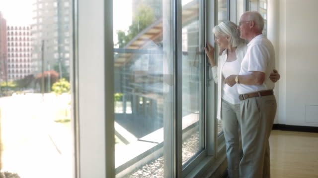 ms pan senior couple looking through window, standing in corridor / vancouver, british columbia, canada - 60 64 years stock videos & royalty-free footage