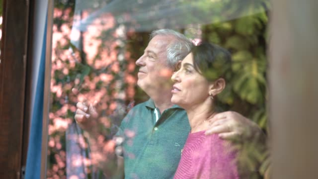 senior couple looking through window - looking through window stock videos & royalty-free footage