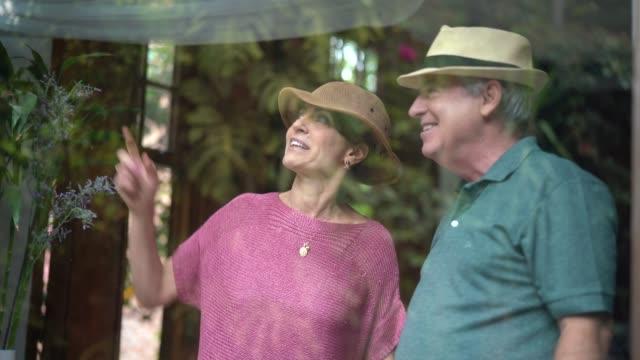 vídeos de stock, filmes e b-roll de casal sênior, olhando pela janela - casal de meia idade