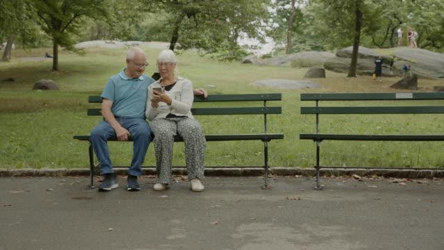 älteres paar lieben bank smartphone social media new york net surfen - sitzbank stock-videos und b-roll-filmmaterial