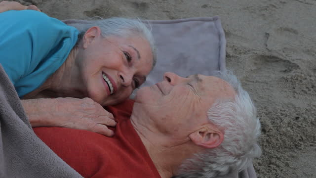 ms senior couple lying together embracing and kissing / los angeles, california, usa - verlieben stock-videos und b-roll-filmmaterial