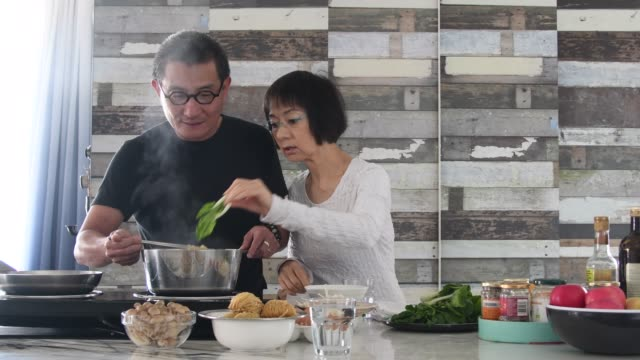 senior couple making lunch together at home in kitchen - occhiali da vista video stock e b–roll