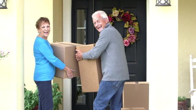vídeos y material grabado en eventos de stock de senior pareja mover el cartón cajas de casa al coche - delante de