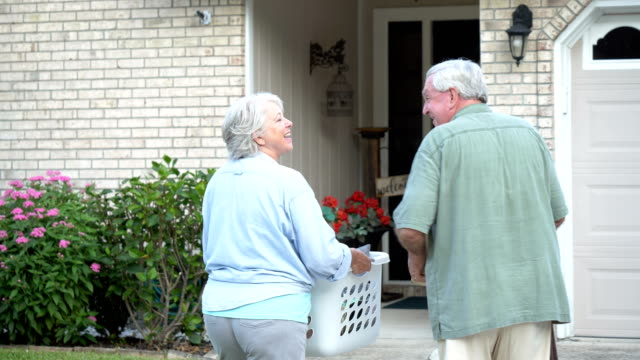 senior couple moving into new house, carrying boxes - 60 69 years stock videos & royalty-free footage