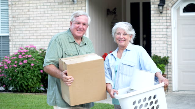 senior couple moving into new house, carrying boxes - downsizing stock videos & royalty-free footage