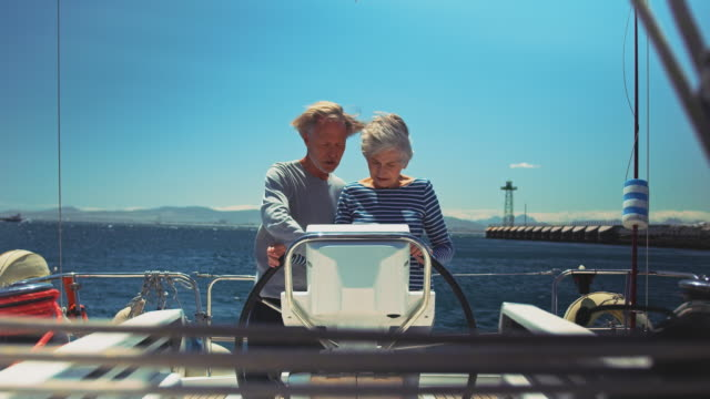 senior couple navigating in yacht during vacation - guidance stock videos & royalty-free footage