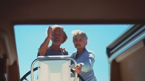 vidéos et rushes de couple de personnes âgées naviguant sur yacht pendant les vacances - montrer la voie