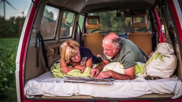 vídeos y material grabado en eventos de stock de senior pareja en un viaje por carretera en su furgoneta camper - tumbado boca abajo