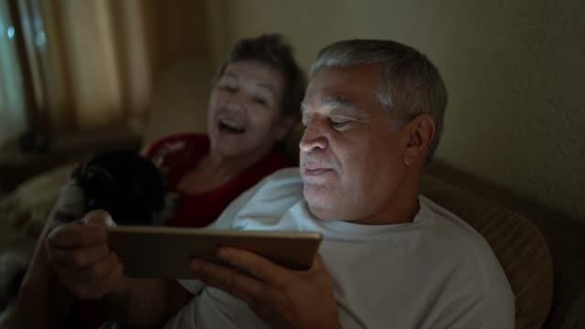 vídeos de stock, filmes e b-roll de casal de idosos em um vídeo chamando usando um tablet digital em casa - distante