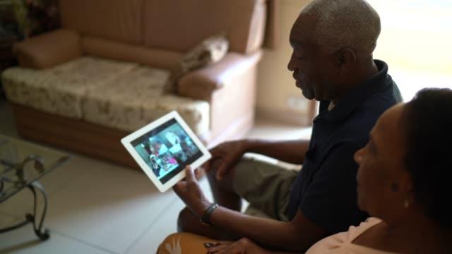 vídeos de stock, filmes e b-roll de casal de idosos em um vídeo chamando usando um tablet digital em casa - quarentena